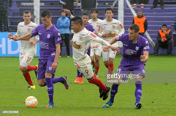 Peruvian Universitario's Raul Ruidiaz vies for the ball with Uruguayan Defensor Sporting's Joaquin Varela and Andres Scotti during their Sudamericana...
