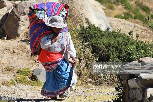 CONTENT] Peruvian woman carrying a heavy rucksack with souvenirs at Colca Canyon in Peru