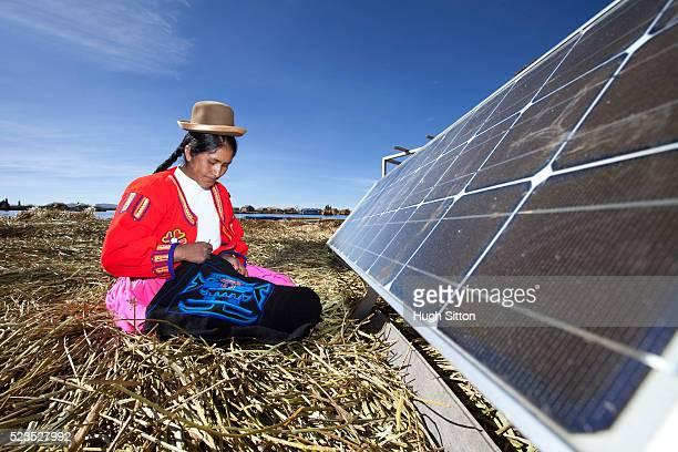 peruvian woman of the uros islands, lake titicaca, with solar panel. puno, peru. - hugh sitton 個照片及圖片檔