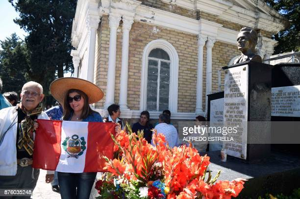 A Peruvian woman poses in front of the Mexican singer and actor Pedro Infante's tomb during the 100th anniversary of his birth at the Panteon Jardin...