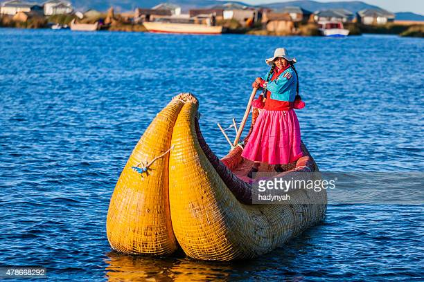 Peruvian woman sailing between Uros floating islands, Lake Tititcaca