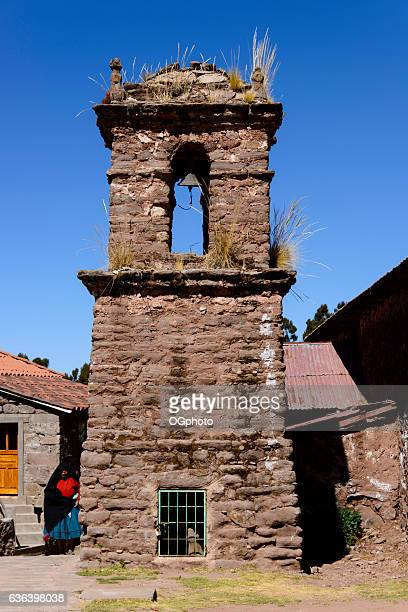 peruvian woman standing next to old stone belfry tower - ogphoto ストックフォトと画像