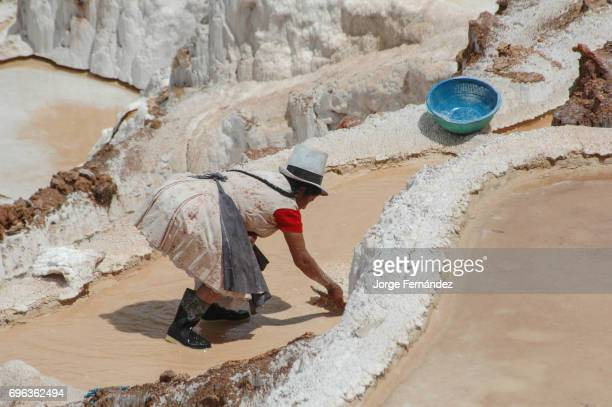 Peruvian woman with traditional hat and hairstyle working on the salt fields of Maras.