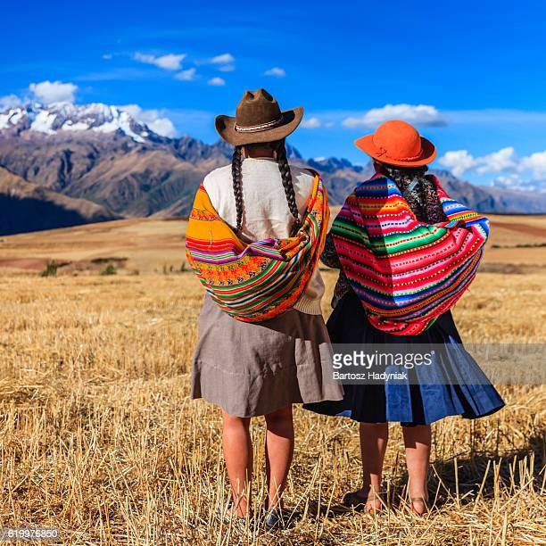 Peruvian women in national clothing crossing field, The Sacred Valley