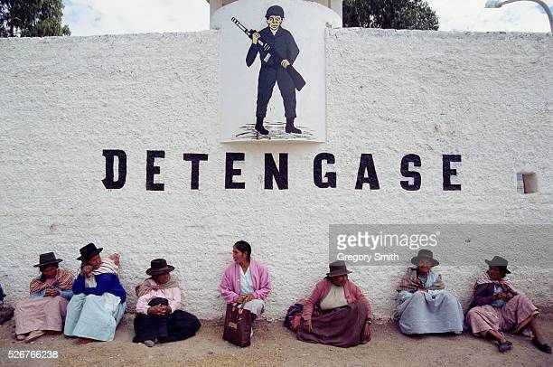 Peruvians sit beneath a sign of a soldier with the word Stop below Peru suffered horrible problems due to the rebel insurgency of the Shining Path |...
