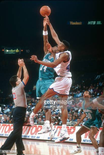 Pervis Ellison of the Washington Bullets battles for a jump ball with JR Reid of the Charlotte Hornets during an NBA basketball game circa 1991 at...