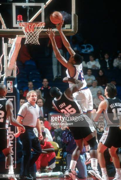 Pervis Ellison of the Washington Bullets shoots over Antoine Carr of the San Antonio Spurs during an NBA basketball game circa 1992 at the Capital...