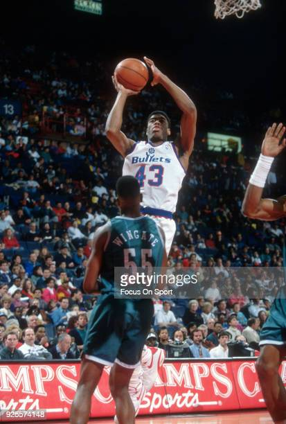 Pervis Ellison of the Washington Bullets shoots over David Wingate of the Charlotte Hornets during an NBA basketball game circa 1992 at the Capital...