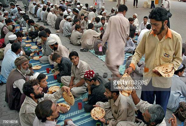A Pakistani Muslim man distributes bread for Iftar at a roadside gathering in Peshawar 26 September 2006 on the second day of the Muslim holy month...