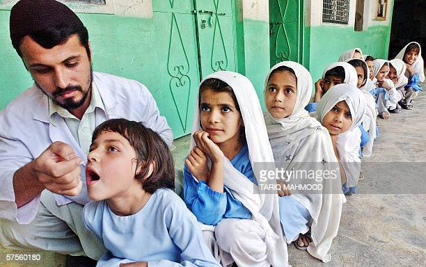 A worker of the International Medical Crops vaccinates an Afghan child against polio in Peshawar 09 May 2006 Pakistan launched a major campaign to...