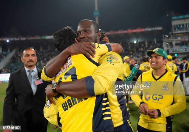 CORRECTION Peshawar Zalmi captain West Indies Darren Sammy celebrates with teammate Wahab Riaz after their victory over Quetta Gladiators in the...