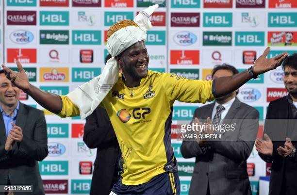 CORRECTION Peshawar Zalmi captain West Indies Darren Sammy wears a traditional turban as he celebrates with teammates his team's victory over Quetta...