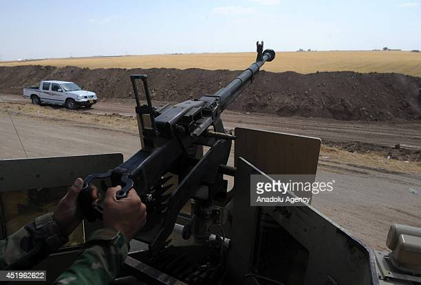 Peshmargas keep watch and aim at armed groups led by Islamic State of Iraq and the Levant on the border that they ditch in Mosul Iraq on 3 July 2014...