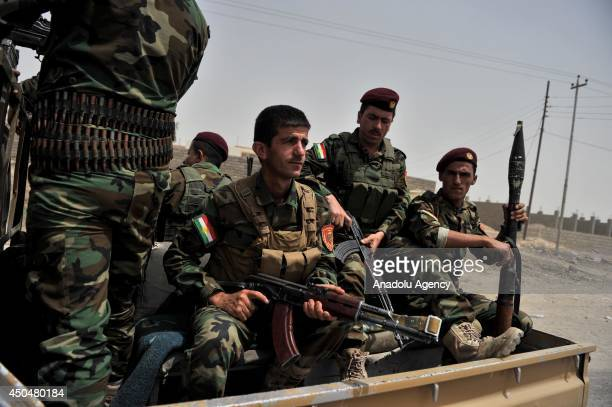 Peshmargas of Iraq Kurdistan Regional Government are seen on the patrol car during patrolling on the outskirts of Mosul to prevent infiltration of...
