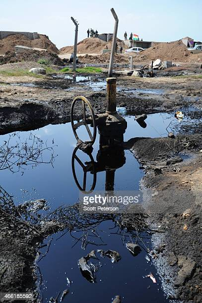 A peshmerga checkpoint is reflected in pools of oil with damaged oil pipeline infrastructure as Iraqi Kurdish forces push the frontline forward...
