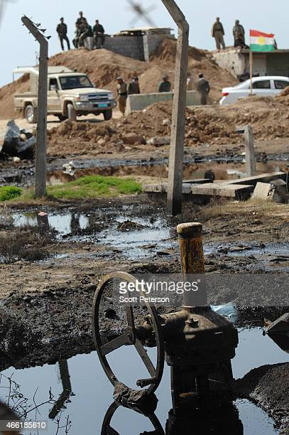 Peshmerga checkpoint is reflected in pools of oil with damaged oil pipeline infrastructure, as Iraqi Kurdish forces push the frontline forward...