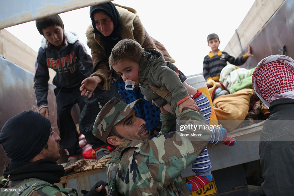 A Peshmerga fighter assists families fleeing their frontline village to a Kurdish-controlled area on November 16, 2015 near Sinjar, Iraq. Peshmerga forces carefully screened displaced Iraqis as they arrived, fearing enemy infiltrators and suicide bombers. Kurdish forces, with the aid of massive U.S.-led coalition airstrikes, liberated Sinjar from ISIL extremists, known in Arabic as Daesh, moving the frontline south. About one thousand villagers in Ghabosyeh fled north to Kurdish held territory, to take refuge camps or onward as refugees to Turkey or Europe.