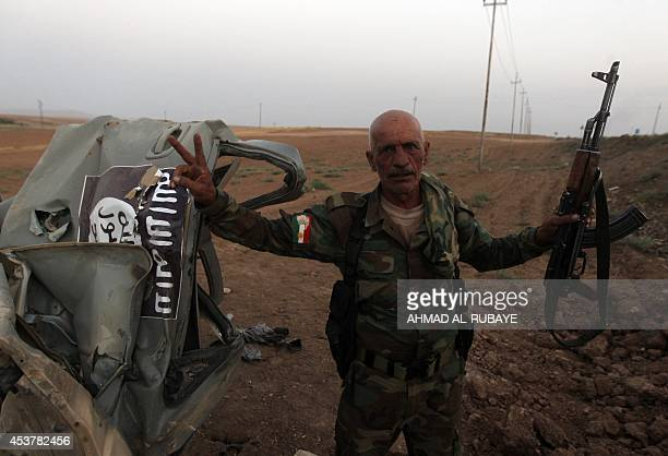 A Peshmerga fighter flashes the sign for victory next to the remains of a car bearing an image of the trademark jihadist flag which reportedly...