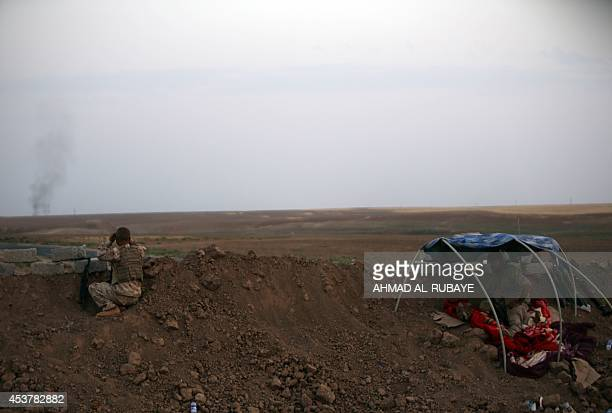 A Peshmerga fighter looks at at smoke rising in the horizon on the front line of fighting with Islamic State militants 20 kilometres east of Mosul on...
