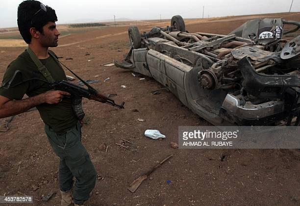 A Peshmerga fighter looks at the remains of a car bearing an image of the trademark jihadist flag which reportedly belonged to Islamic State...