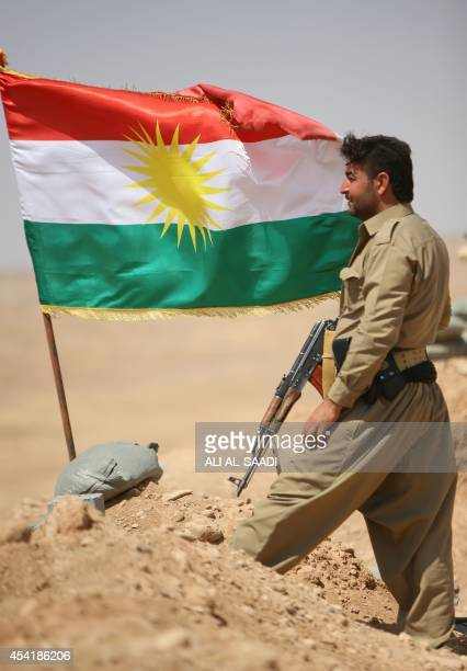 A peshmerga fighter stands next to a Kurdish flag as he guards a position near the strategic Jalawla area in Diyala province which is a gateway to...
