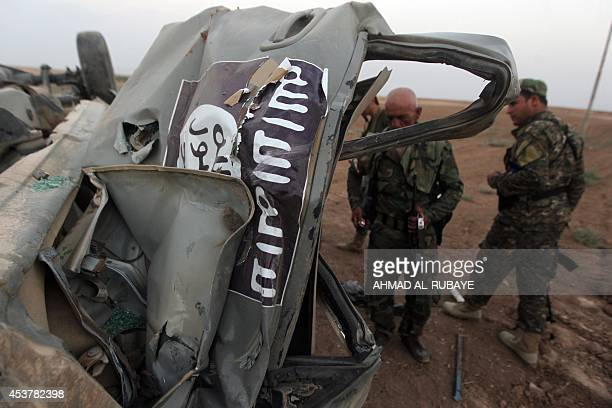 Peshmerga fighters inspect the remains of a car bearing an image of the trademark jihadist flag which belonged to Islamic State militants after it...