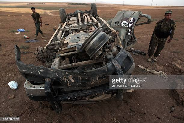 Peshmerga fighters inspect the remains of a car bearing an image of the trademark jihadist flag which reportedly belonged to Islamic State militants...