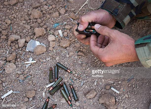 Peshmerga fighters loads the magazin of AK47 on the front line close to Bashiqa city 30km from Mosul in Iraq 3 June Bashiqa Kurdish Iraq Autonomy