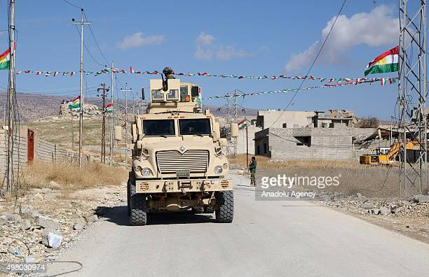 Peshmerga forces belonging to the Kurdish Regional Government in armored vehicle patrol the Sinjar town of Mosul Iraq on November 20 2015 after...