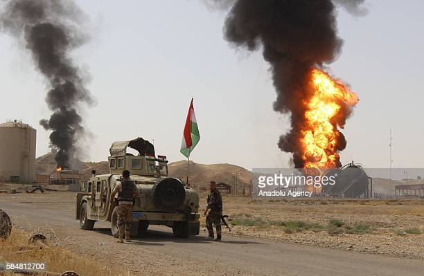 Peshmerga forces take security measures as smoke and flames rise after Daesh's attack on an oilwell in Kirkuk's Bay Hassan village Iraq on July 31...