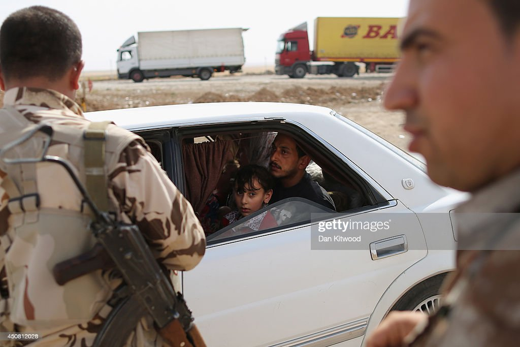 Peshmerga military direct traffic at a Kurdish Check point on June 14, 2014 in Kalak, Iraq. Thousands of people have fled Iraq's second city of Mosul after it was overrun by ISIS (Islamic State of Iraq and Syria) militants. Many have been temporarily housed at various IDP (internally displaced persons) camps around the region including the area close to Erbil, as they hope to enter the safety of the nearby Kurdish region.