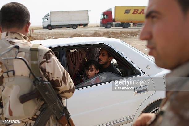 Peshmerga military direct traffic at a Kurdish Check point on June 14, 2014 in Kalak, Iraq. Thousands of people have fled Iraq's second city of Mosul...
