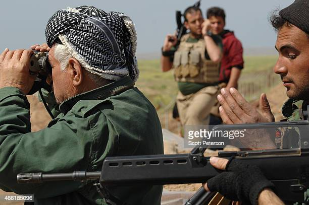 A peshmerga officer uses binoculars as Iraqi Kurdish forces push the frontline forward against ISIS forces in the Tal alWard district 20 miles...
