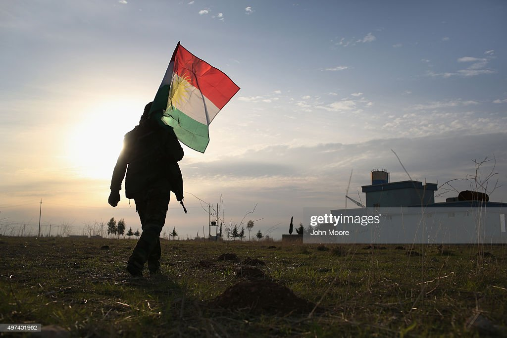 A Peshmerga soldier walk to place a Kurdish flag near the frontline with ISIL on November 16, 2015 in Sinjar, Iraq. Kurdish forces, with the aid of massive U.S.-led coalition airstrikes, liberated the town from ISIL extremists, known in Arabic as Daesh, in recent days. Although many minority Yazidis celebrated the victory, their home city of Sinjar lay in almost complete ruins.