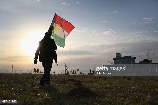 Peshmerga soldier walk to place a Kurdish flag near the frontline with ISIL on November 16 2015 in Sinjar Iraq Kurdish forces with the aid of massive...