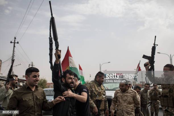 Peshmerga soldiers fire their guns in the air to celebrate the referendum on the road outside a voting station on September 25, 2017 in Kirkuk, Iraq....