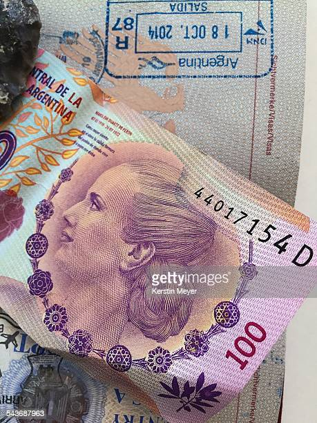 100 peso from Argentina with Evita Peron the note is lying in a passport and you can see the visa stamp