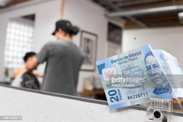 A 20 peso note is clipped to the mirror as barber Josue 'Sway' Navarro works on Denver Nuggets guard Jamal Murray at Bellwether Barbershop on...