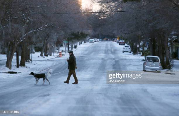A peson walks his dog through a snow covered street as snow that fell yesterday and cold weather blanket the area on January 4 2018 in Savannah...