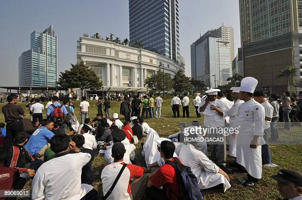 Pesonnel of RitzCarlton hotel are evacuated in the open field across the bombed hotel in Jakarta on July 17 2009 after explosion hit RitzCarlton and...