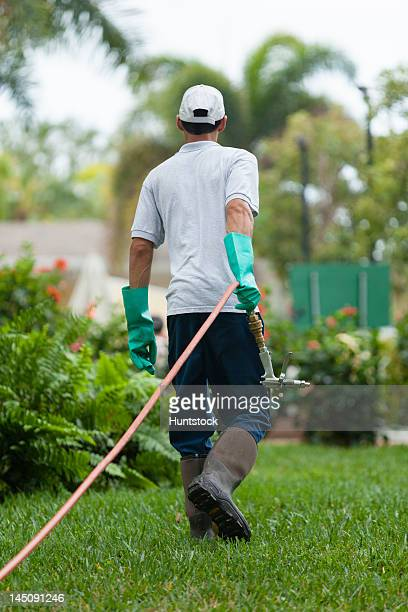 Pest control technician pulling high pressure spray gun and hose with heavy duty gloves
