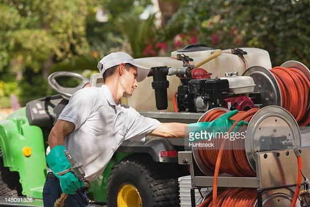 pest control technician pulling hose from reel in service truck - tee reel bildbanksfoton och bilder