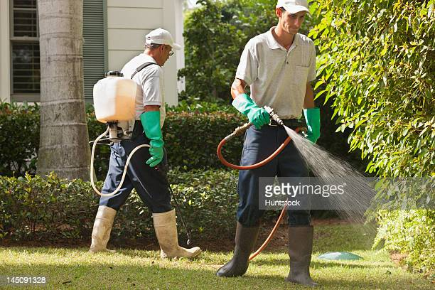 Pest control technicians using portable spray rig on tree and grass environment