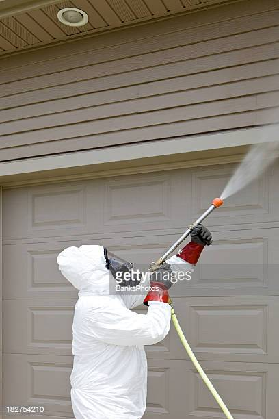 pest control worker spraying insecticide on a home's garage - white suit stock pictures, royalty-free photos & images