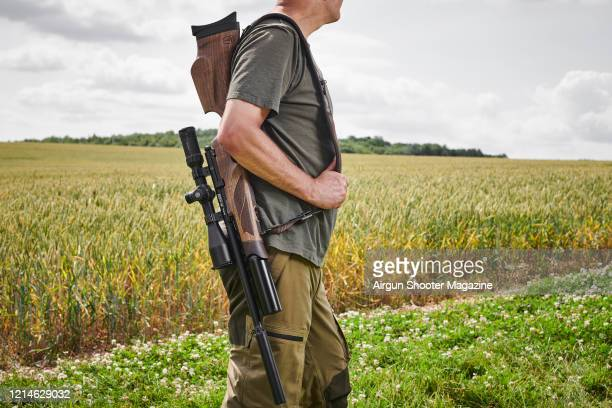 Pest controller with an air rifle photographed in a field in Hampshire, taken on July 7, 2019.