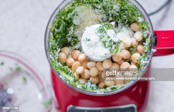 pesto preparation with macademia nuts. - macadamia nut stock photos and pictures