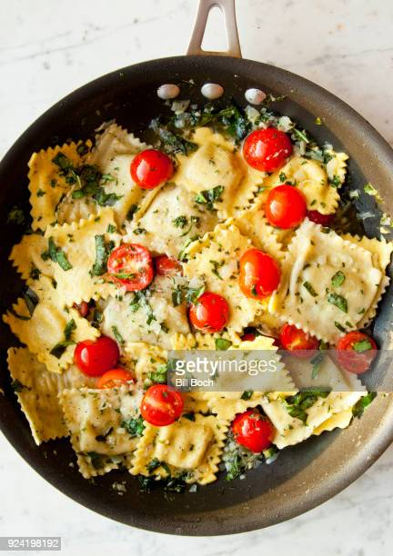 pesto ravioli with cherry tomatoes in a saute pan with chopped flat leaf parsley - flat leaf parsley stock photos and pictures