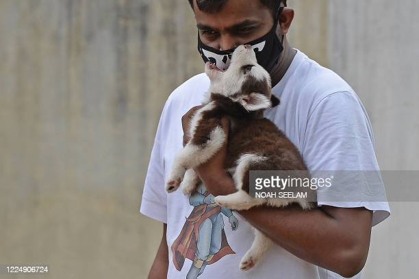Pet owner holds his dog as he waits for its vaccination at a government veterinary hospital on World Zoonoses Day in Hyderabad on July 6, 2020. -...