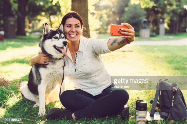pet owner with dog taking selfie - off leash dog park stock pictures, royalty-free photos & images