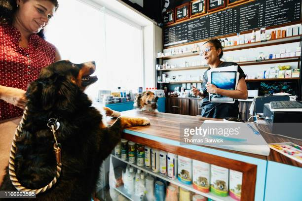 Pet store owner greeting dog and owner at counter in pet store